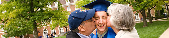 parents kissing graduate